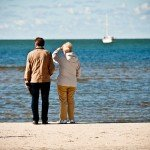 Estate planning elderly couple on seashore looking boat at the sea